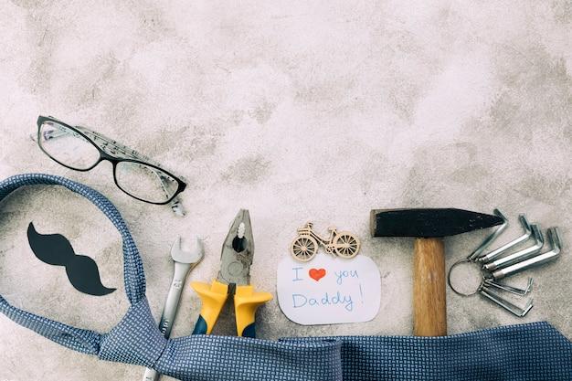 Verzameling van instrumenten in de buurt van decoratieve snor met ik hou van je vader woorden en stropdas