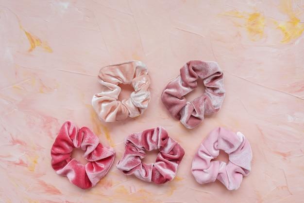 Verzameling van trendy fluwelen scrunchies op roze, plat leggen