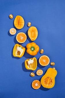 Verzameling van verse gele groenten en fruit op de blauwe achtergrond