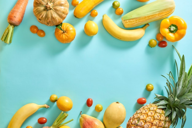 Verzameling van verse gele groenten en fruit op de lichtblauwe achtergrond