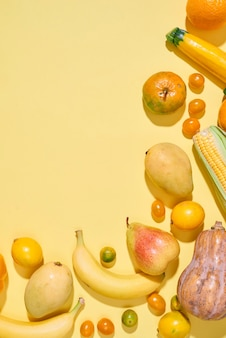 Verzameling van verse gele groenten en fruit op de lichtgele achtergrond