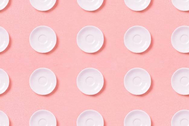 Verzameling van witte kleine platen op een roze oppervlak. patroon bovenaanzicht