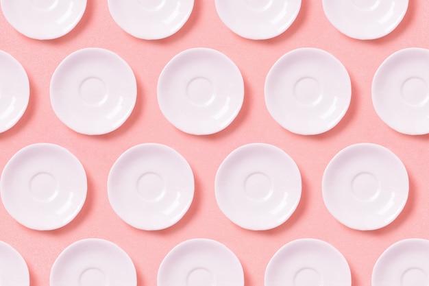 Verzameling van witte kleine platen op een roze oppervlak.