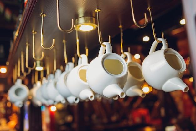 Verzameling vintage authentieke cooper schalen, keukengerei op hangend pottenrek, kransachtige wilgenhanger, daglicht.