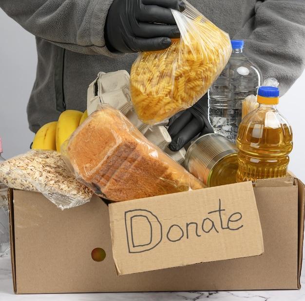 Verzamelt voedsel, fruit en dingen in een kartonnen doos om de behoeftigen en de armen te helpen, het concept van hulp en vrijwilligerswerk