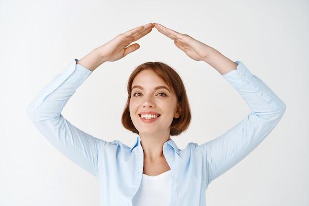 Verzekering en onroerend goed concept. glimlachende vrouw in blouse die handdak over hoofd maakt, huisgebaar toont, staande op witte muur