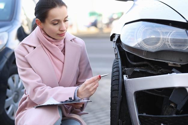 Verzekeringsagent houdt een schatting van de waarde van het beschadigde voertuig