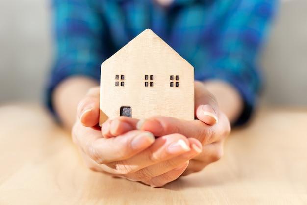 Verzekeringsbeschermende dekking van het huis en huis om in de hand te zorgen met het financiële en verzekeringsconcept van onroerendgoedzaken tot succes voor huur, investeren en het redden van een gelukkig gezinslevenconcept