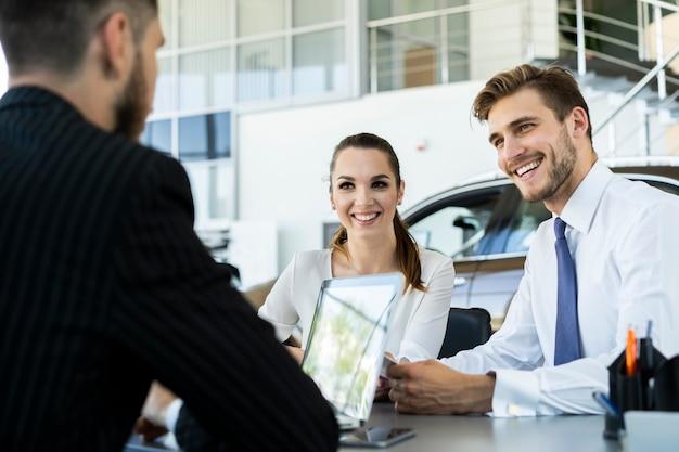 Verzekeringsmakelaar of verkoper die aanbod doet aan jong stel, makelaar die klanten raadpleegt over hypotheek