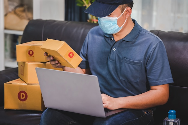 Verzenden online winkelen eigenaren van kleine bedrijven schrijven op kartonnen dozen op het werk voor kleine mkb-ondernemers impact van de crisis covid-19 online verkoopactiviteiten