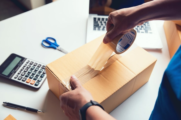 Verzending online verkoop. man werknemer bezorgservice en werkende verpakking, bedrijfseigenaar werkt het controleren van de bestelling om te bevestigen voordat hij de klant in de post stuurt