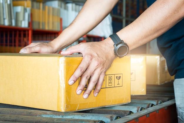 Verzending, pakketbakken, werknemer sorteren pakketdozen op transportband bij distributie magazijn.