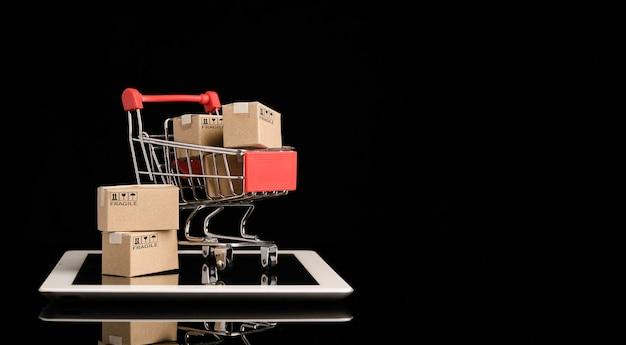 Verzending van papieren dozen in rode winkelwagen trolley op tablet met zwarte achtergrond en kopieer ruimte, online winkelen en e-commerce concept.