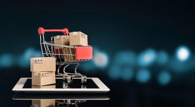 Verzending van papieren dozen in rode winkelwagen trolley op tablet met zwarte en blauwe bokeh achtergrond en kopieer ruimte, online winkelen en e-commerce concept.
