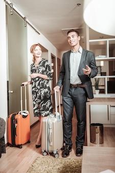 Verzorgende bagage. goed uitziende liefhebbende man en vrouw die voor hun bagage zorgen bij het betreden van de hotelkamer