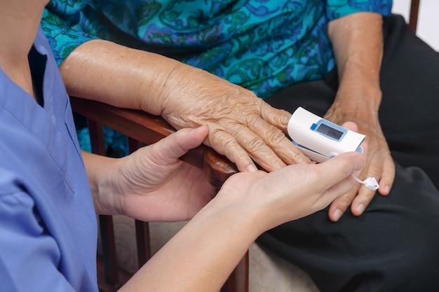 Verzorger controleert de zuurstofsaturatie bij de vingertop van een oudere vrouw.