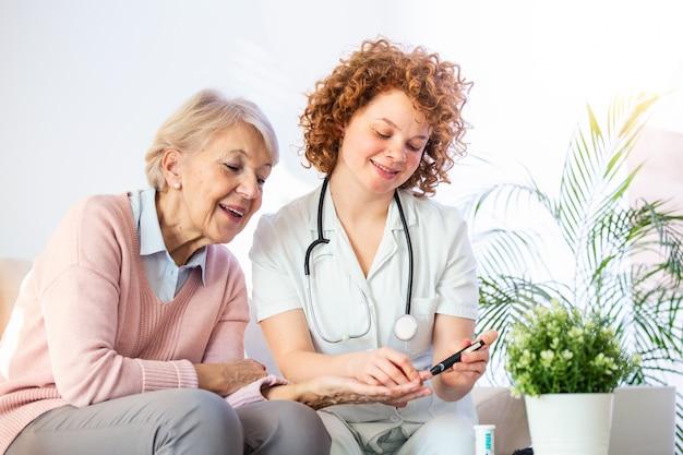 Verzorger die bloedsuiker van hogere vrouw thuis meet. diabetes en glicemie concept