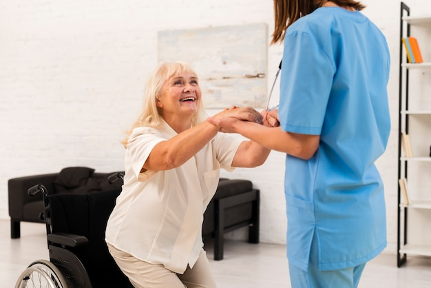 Verzorger die oude vrouw helpt