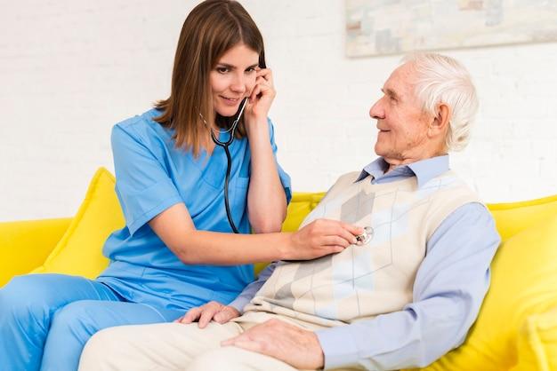 Verzorger die stethoscoop op de oude mens met behulp van