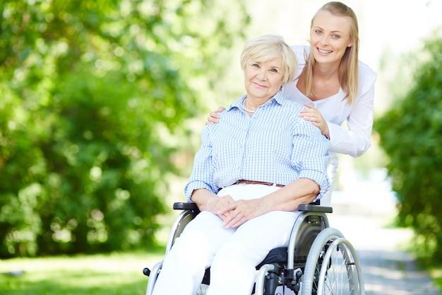 Verzorger duwen hooggeplaatste vrouw in rolstoel