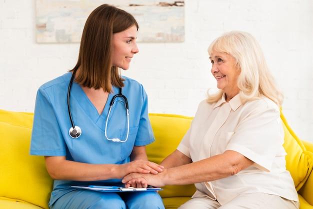 Verzorger en oude vrouw hand in hand