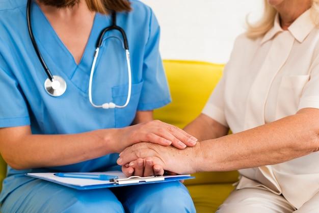 Verzorger en oude vrouwenholding overhandigt close-up