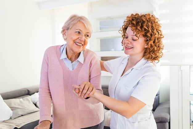 Verzorger en senior vrouw lopen samen thuis