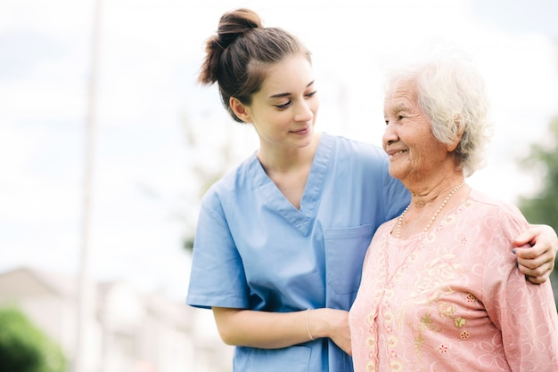 Verzorger met aziatische bejaarde openlucht