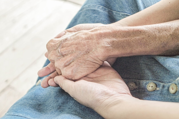 Verzorger, verzorger hand met oudere hand in hospice zorg