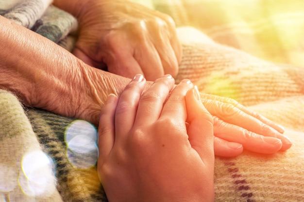 Verzorger, verzorger hand met oudere hand
