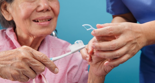 Verzorger zorg voor aziatische oudere vrouw tijdens het gebruik van tandheelkundige stok.