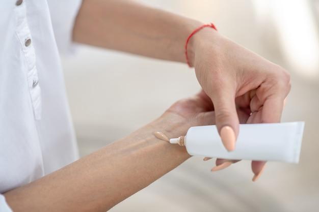 Verzorging cosmetica. close-up van jonge vrouw hand proberen cosmetische verzorgingsproduct uit buis van gezicht niet zichtbaar