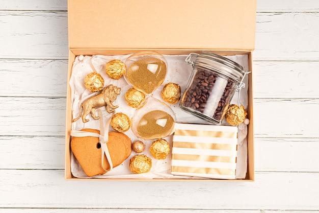 Verzorgingspakket voorbereiden, seizoensgebonden geschenkdoos met koffie, koekjes en chocolaatjes. gepersonaliseerde milieuvriendelijke kerstmand voor familie en vrienden in gouden kleuren.