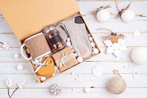 Verzorgingspakket voorbereiden, seizoensgebonden geschenkdoos met thee, koekjes en wollen sokken. gepersonaliseerde milieuvriendelijke mand voor familie en vrienden voor kerstmis. bovenaanzicht, plat gelegd