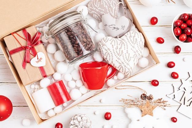 Verzorgingspakket voorbereiden, seizoensgeschenkdoos met koffie, kaarsen en beker in rode en witte kleuren. gepersonaliseerde milieuvriendelijke mand voor familie en vrienden voor kerstmis. bovenaanzicht, plat gelegd