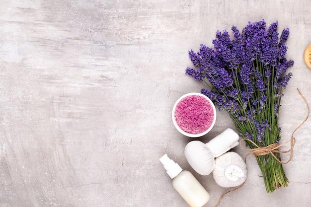 Verzorgingsproducten en vers lavendelboeket op witte houten lijst.