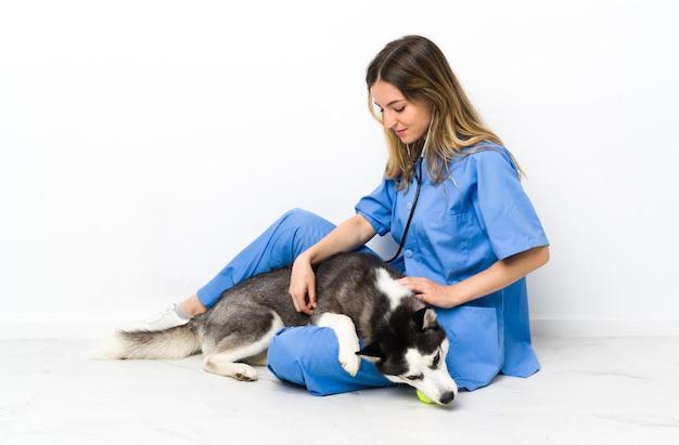 Veterinaire arts bij dierenartskliniek met siberische schor hond