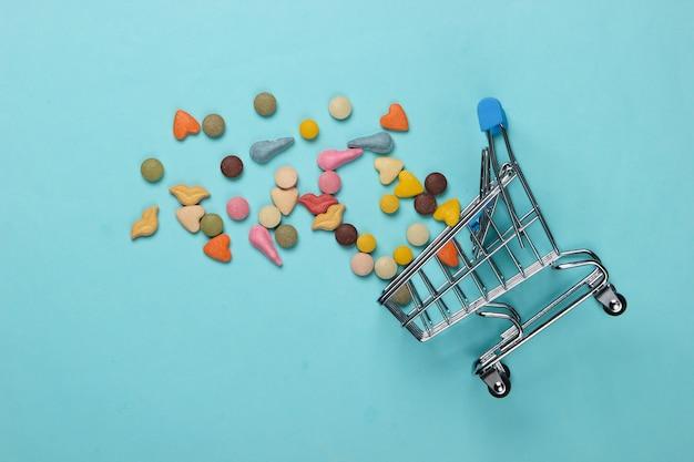 Veterinaire tabletten van vitamines met verschillende vormen voor katten en winkelwagentje op blauw