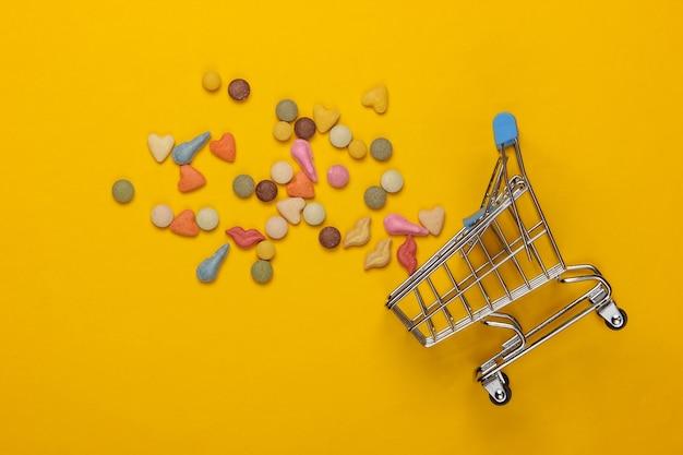 Veterinaire tabletten van vitamines met verschillende vormen voor katten en winkelwagentje op een gele