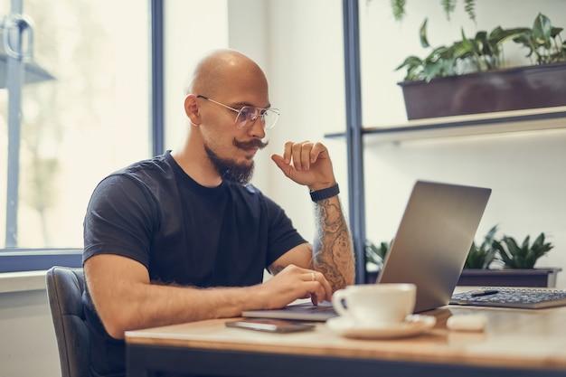 Vetgedrukte man met snor en baard werkt op de computer thuis, programmeur, schrijver, freelancer
