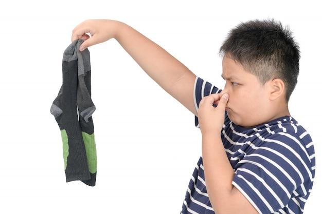 Vette jongen die vuile stinkende geïsoleerde voetbalsokken houden
