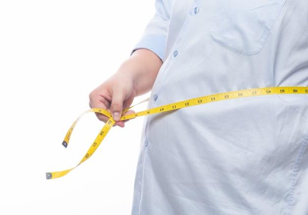 Vette mens die een metingsband houdt voor controle zijn geïsoleerd lichaam