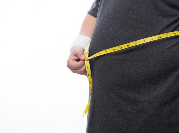 Vette mens die een metingsband houdt voor controle zijn lichaam dat op witte achtergrond wordt geïsoleerd