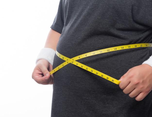 Vette mens die een metingsband houdt voor controle zijn lichaam dat op witte muur wordt geïsoleerd