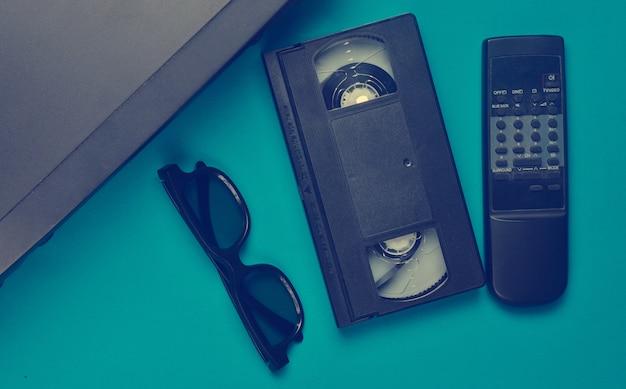Vhs-speler, videocassette, 3d-bril, tv-afstandsbediening op een blauw oppervlak