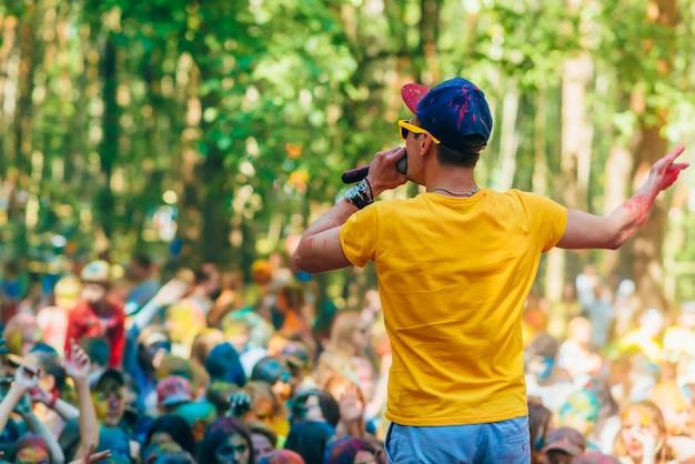 Vichuga, rusland - juni 17, 2018: man leidt tribunes op het stadium bij de viering van het festival van kleuren holi