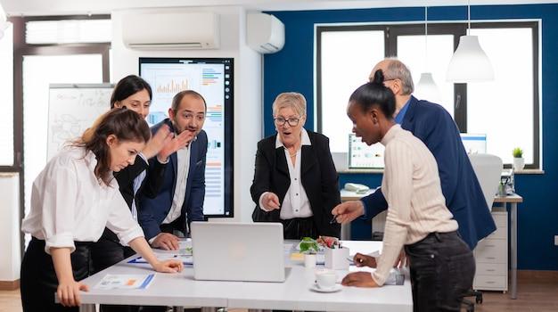 Victorius mixte startup-team dolblij in vergaderruimte na geweldig zakelijk project