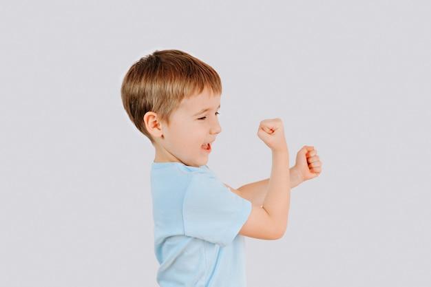 Victory schreeuwend kind. portret van emotionele blanke jongetje schreeuwen met zijn handen omhoog