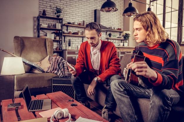 Video aan het kijken. twee muzikanten zitten aan tafel en kijken naar muziekvideo op zilveren laptop in loft