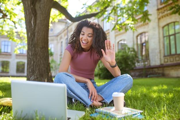 Video-oproep. een glimlachend opgewonden meisje dat op het gras zit en een videogesprek voert